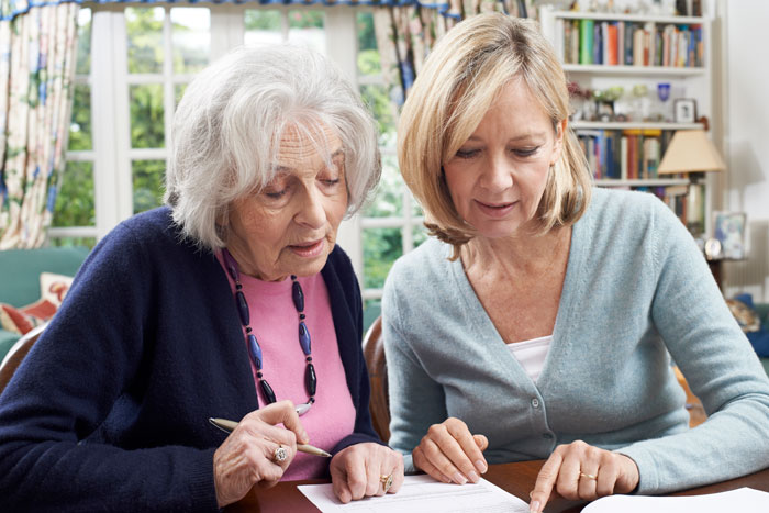 elderly woman receiving help signing up for medigap coverage with forms from her daughter