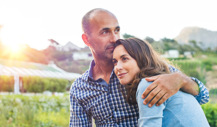 couple happy with the future thanks to supplemental health insurance taking a walk on a country road