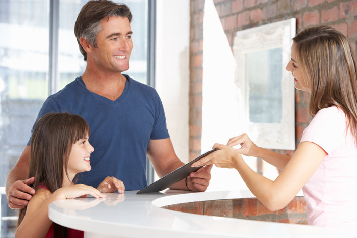 man with young daughter at doctors office doing paperwork smiling