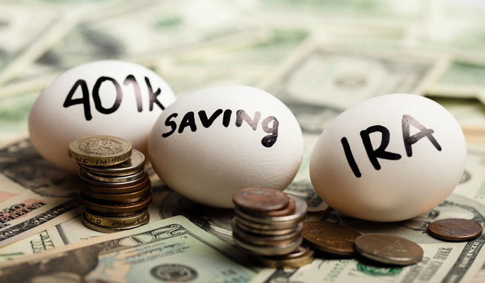 Three eggs with 401(k) saving and IRA written on them laying on top of dollar bills and coins